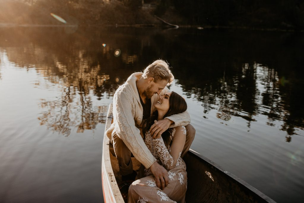 Photo of couple sitting in canoe with sun shining on them